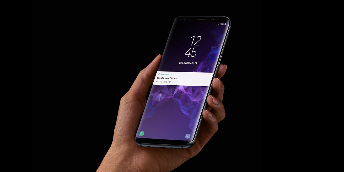 A person holding a Galaxy S9 Midnight Black with his left hand, receiving a 'Buy concert tickets' notification from Bixby Reminder.