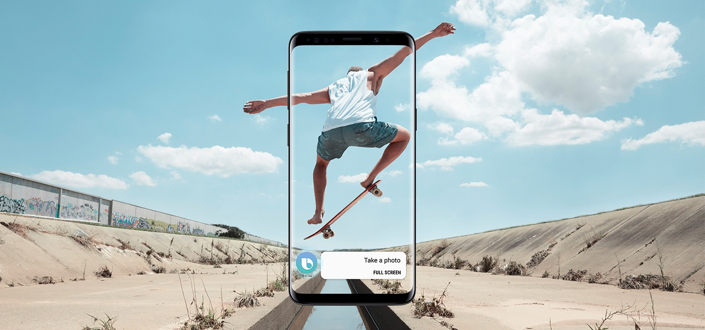 A man performs a skateboard jump over a causeway. A front view of Galaxy S9 Midnight Black displaying the message 'Take a photo' on screen