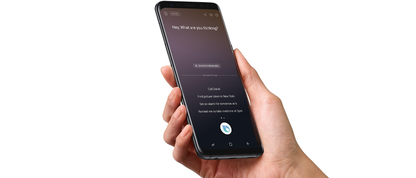 A right hand holding the Galaxy S9 Midnight Black on which Bixby Voice is running
