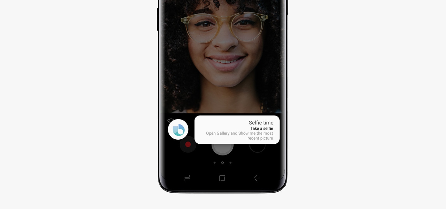 A front view of Galaxy S9 Midnight Black with a selfie of a girl. A Customised Quick Command named 'Selfie Time' is running with a sequence of action messages including 'Take a selfie' and 'Open Gallery and Show me the most recent picture'.