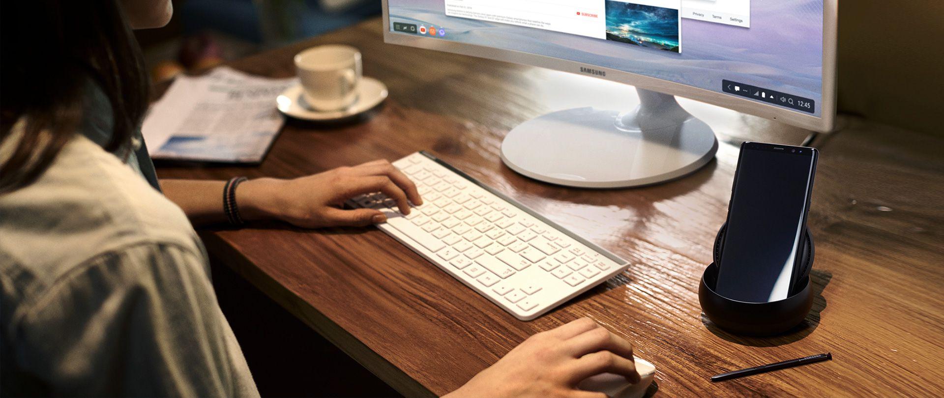 Immagine di una persona che usa Galaxy Note8 e DeX Station sulla scrivania con monitor, tastiera e mouse Samsung