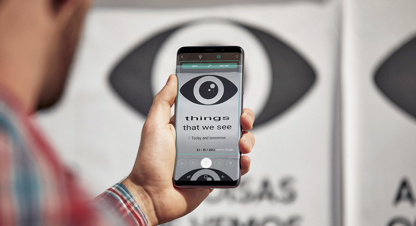 Image of a person holding Galaxy S9+ with a translated sign on-screen and the untranslated photo in the background