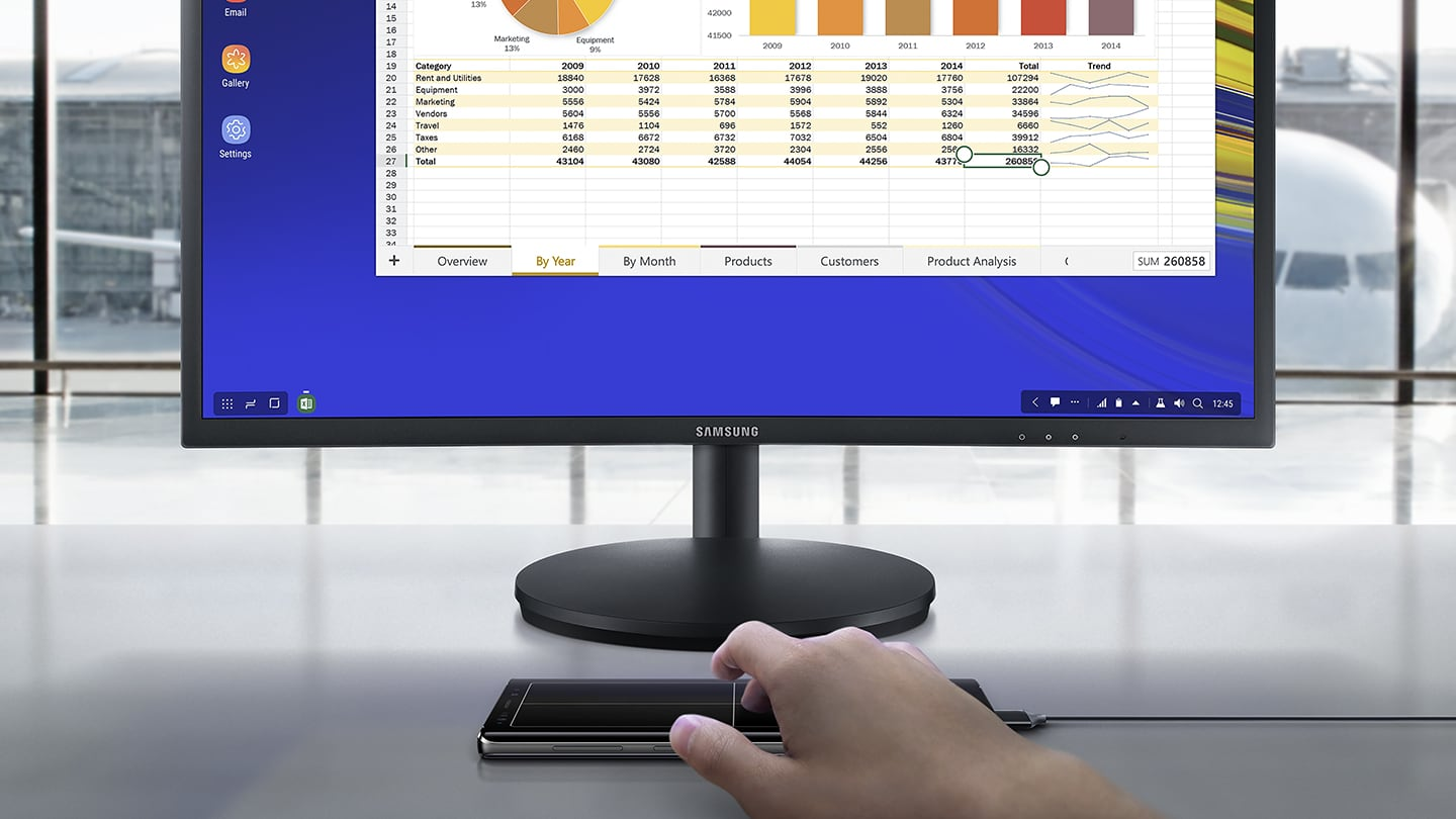 Simulated image of a person using Galaxy Note9 connected to Samsung DeX via a single cable, looking at a spreadsheet on the connected monitor and using Galaxy Note9 as a touchpad