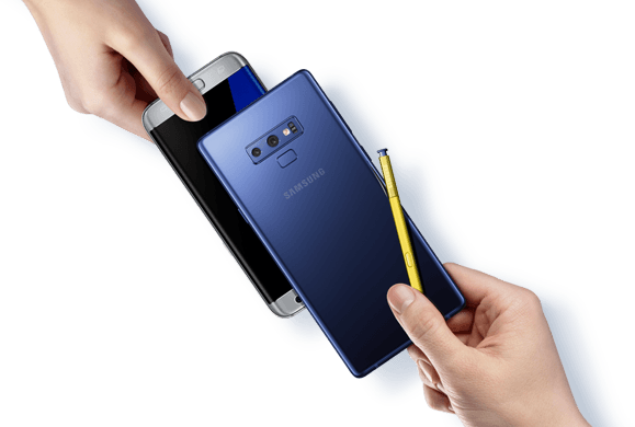 A hand on the left holding an older silver Galaxy phone underneath a hand on the right holding the Ocean Blue Galaxy Note9 and yellow S Pen