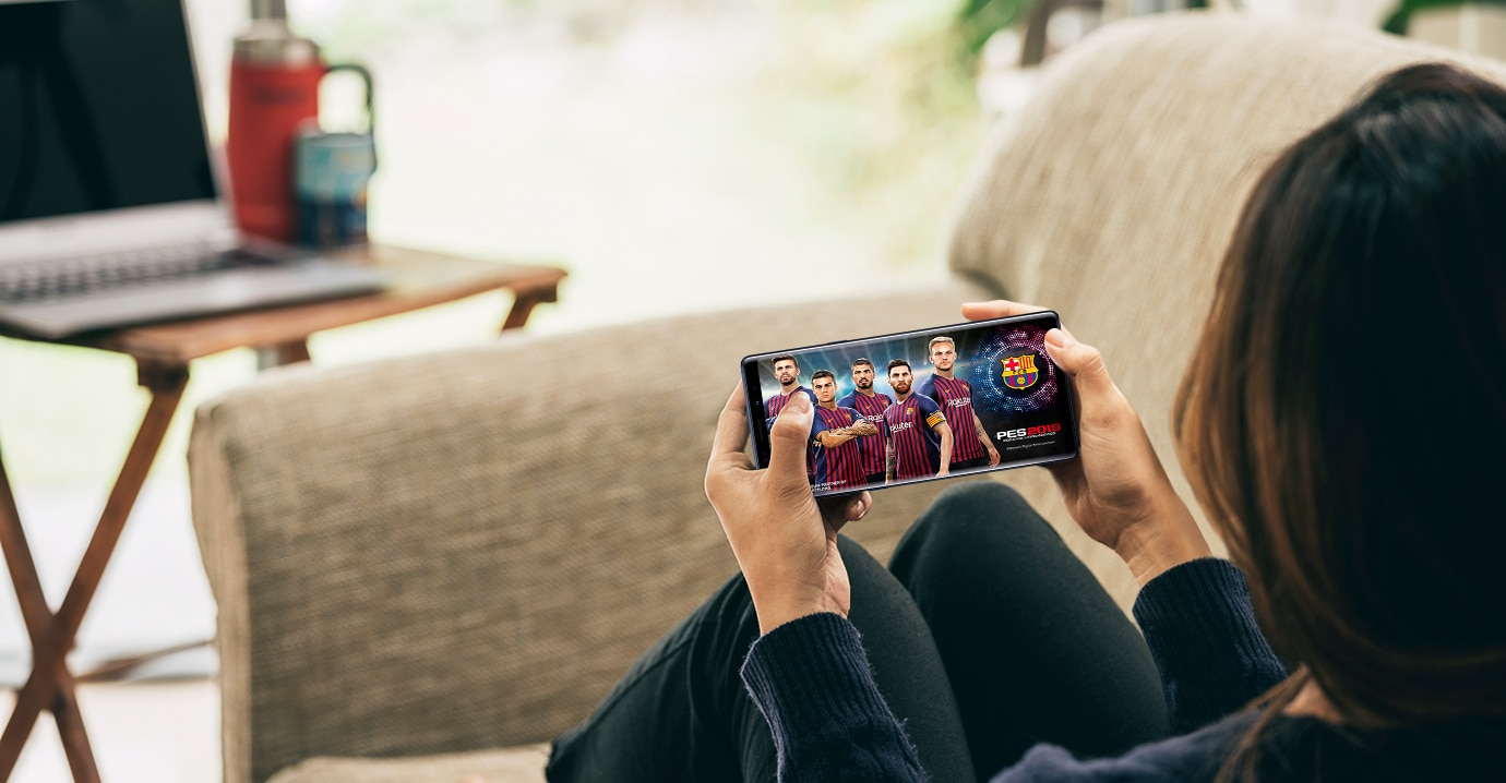 Image of a woman sitting on her couch playing a game via Steam Link on the Galaxy Note9
